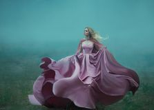 La bionda nella nebbia in un vestito reale costoso lungo leggero che fluttua in moto, prende la forma di un fiore magico, a fotografia stock