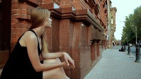 La bionda sola affascinante si siede sulla via in un vestito nero stock footage