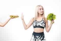 La bionda sportiva rifiuta gli alimenti a rapida preparazione immagine stock