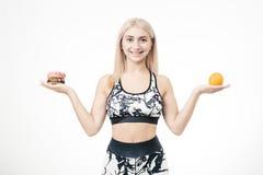 La bionda sportiva tiene in sua mano un hamburger e un'arancia fotografia stock libera da diritti