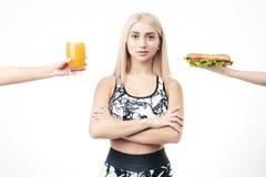 La bionda sportiva tiene in sua mano un hamburger e un vetro di succo fresco fotografia stock libera da diritti