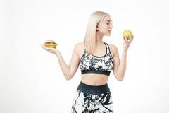 La bionda sportiva tiene in sue mani un hamburger e una mela fotografia stock