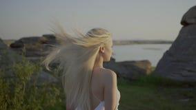 La bionda sta avendo una passeggiata sulla riva del lago stock footage