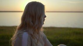 La bionda sta esaminando il tramonto stock footage