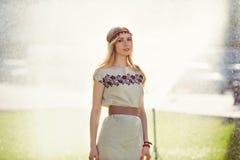 La bionda tenera della donna cammina sull'erba sui precedenti di innaffiatura del prato inglese, vestiti in un vestito naturale,  Fotografia Stock Libera da Diritti