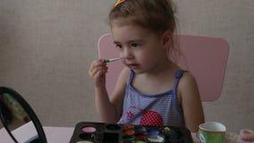 La bionda tre bande di colore della pittura del bambino di anni sul suo fronte che esamina lo specchio si siede dalla tavola archivi video