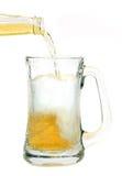La bière a plu à torrents dans la tasse en verre Photos stock