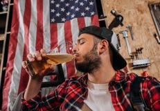 la birra bevente della riparazione del lavoratore bello della stazione al garage con gli S.U.A. inbandiera l'attaccatura fotografia stock libera da diritti