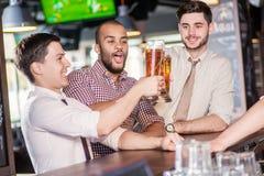 La birra della bevanda degli uomini e gode del soggiorno Altri tre uomini che bevono birra Fotografia Stock Libera da Diritti