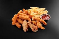La birra fresca fa un spuntino l'assortimento dei bastoni del formaggio delle patate fritte delle ali di pollo sul nero fotografia stock