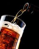 La birra sta versando in un vetro dalla bottiglia su fondo nero immagini stock libere da diritti