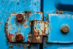 La bisagra de puerta de un coche azul aherrumbró las nueces abandonadas imagen de archivo