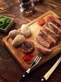 La bistecca arrostita della carne di maiale incide le fette su un supporto di legno Fotografia Stock