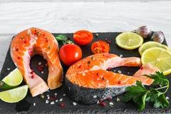 La bistecca di color salmone cruda con le spezie, le erbe, i pomodori ed il limone sull'ardesia nera imbarcano sopra fondo di leg immagini stock libere da diritti