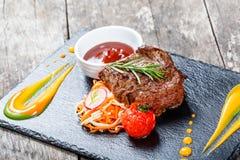 La bistecca di manzo arrostita con insalata fresca ed il bbq sauce sul fondo di pietra dell'ardesia su fondo di legno Immagini Stock Libere da Diritti