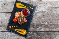 La bistecca di manzo arrostita con insalata fresca ed il bbq sauce sul fondo di pietra dell'ardesia su fondo di legno Immagine Stock Libera da Diritti
