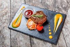 La bistecca di manzo arrostita con insalata fresca ed il bbq sauce sul fondo di pietra dell'ardesia su fondo di legno Fotografia Stock