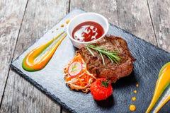 La bistecca di manzo arrostita con insalata fresca ed il bbq sauce sul fondo di pietra dell'ardesia su fondo di legno Fotografia Stock Libera da Diritti