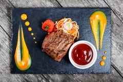 La bistecca di manzo arrostita con insalata fresca ed il bbq sauce sul fondo di pietra dell'ardesia su fondo di legno Immagini Stock