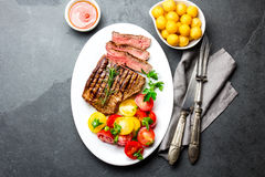 La bistecca di manzo arrostita rara media affettata è servito sul piatto bianco con l'insalata del pomodoro e le palle delle pata immagine stock