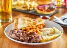 La bistecca e le uova fanno colazione con le patate del homestyle e del pane tostato in ristorante immagine stock