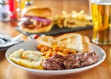 La bistecca e le uova fanno colazione con le patate del homestyle e del pane tostato in ristorante fotografia stock libera da diritti