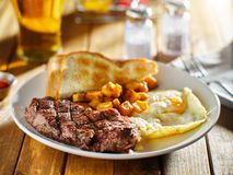 La bistecca e le uova fanno colazione con le patate del homestyle e del pane tostato in ristorante immagine stock libera da diritti