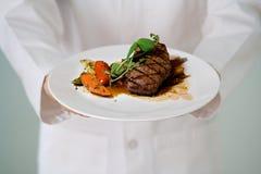La bistecca sugosa è servito dal cuoco unico Immagine Stock
