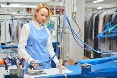La blanchisserie de travailleur repassée vêtx le fer sec photos libres de droits