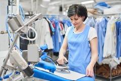 La blanchisserie de travailleur repassée vêtx le fer sec photo stock