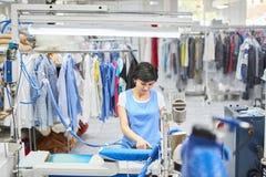 La blanchisserie de travailleur repassée vêtx le fer sec Images libres de droits
