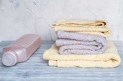 La blanchisserie a placé avec des serviettes et des bottels de plastique sur le fond gris photographie stock