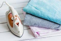 La blanchisserie a placé avec les serviettes et le fer sur le fond blanc photo libre de droits