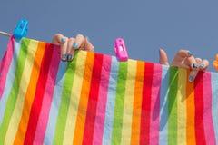 La blanchisserie propre est accrochée par une femme pour sécher images libres de droits