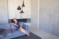La blonde éblouissante utilise le smartphone et essaye la fraise mûre, sitti Images libres de droits