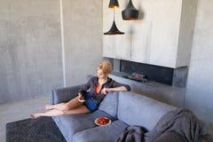 La blonde éblouissante utilise le smartphone et essaye la fraise mûre, sitti Photographie stock
