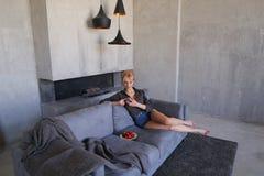La blonde éblouissante utilise le smartphone et essaye la fraise mûre, sitti Photos stock