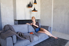 La blonde éblouissante utilise le smartphone et essaye la fraise mûre, sitti Photo stock