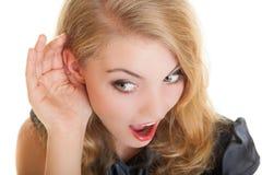 La blonde a étonné la fille de bavardage avec la main derrière le secret de écoute d'oreille photos stock