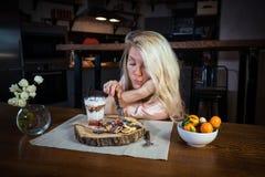 La blonde attirante s'assied à la table avec la nourriture contre la cuisine moderne en appartement élégant images libres de droits