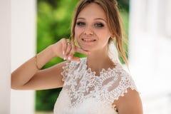 La blonde aux yeux bleus dans une dentelle a brodé la robe posant dans la photo Une fille regarde l'appareil-photo et sourit avec Photographie stock libre de droits
