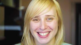 La blonde avec différents yeux regarde l'appareil-photo et enlève sa main, heterochromia, dans le mouvement lent banque de vidéos