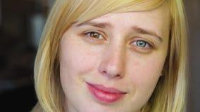 La blonde avec différents yeux regarde l'appareil-photo et les sourires, heterochromia banque de vidéos
