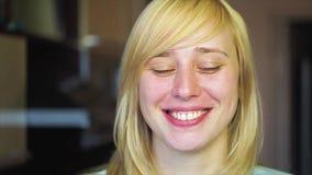 La blonde avec différents yeux regarde l'appareil-photo et les sourires, heterochromia, dans le mouvement lent banque de vidéos