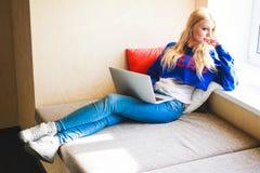 La blonde avec l'ordinateur portable dans le bureau moderne regardant le vent Images libres de droits