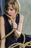 La blonde avec les cheveux courts dans des combinaisons bleues avec la dentelle gaine mordre la corde enroulée autour de elle Photo libre de droits
