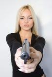La blonde avec un pistolet Image stock