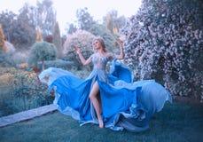 La blonde, avec une belle coiffure élégante, marche dans un jardin de floraison fabuleux Princesse dans une longue robe gris-bleu image libre de droits