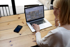 La blonde d'étudiant s'assied à un ordinateur portable dans un café Images libres de droits