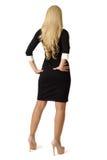 La blonde dans la robe noire se tient avec le sien de retour Photographie stock libre de droits